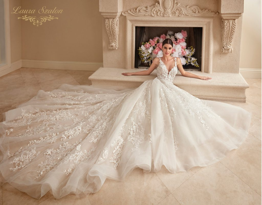 Gyönyörű csipkés menyasszonyi ruhában van a modell a kandalló előtt.