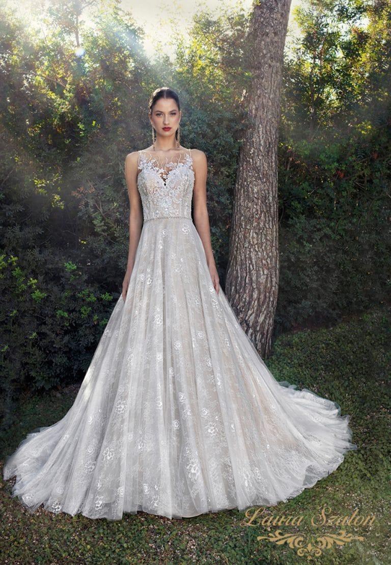 A-vonalú menyasszonyi ruhában áll a hölgy egy fa előtt.