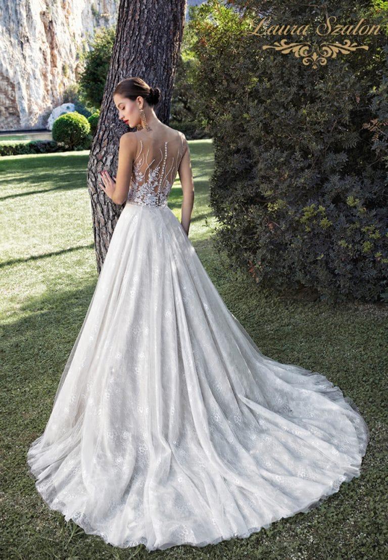 Klasszikus Demetrios menyasszonyi ruha háta látszik a képen egy fa előtt.
