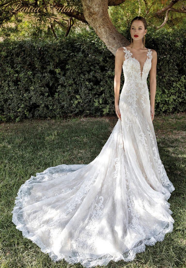 Bérelhető menyasszonyi ruhában pózol a modell a bokrok előtt.