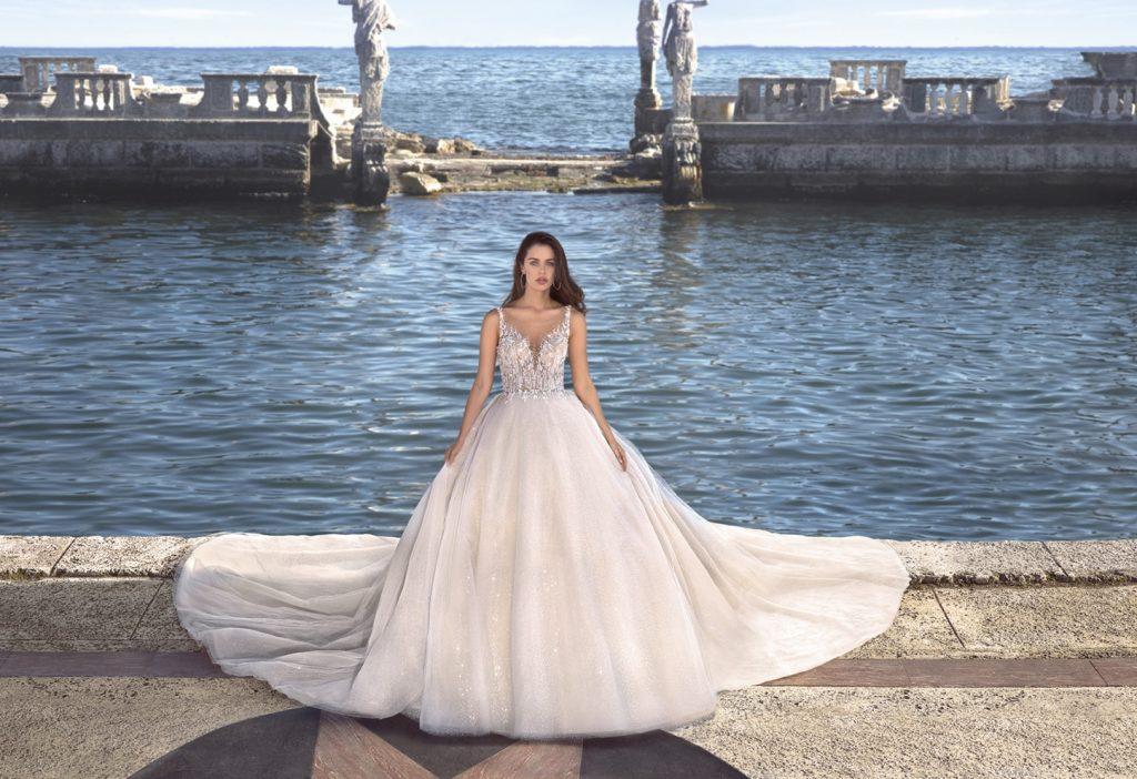 Nagyszoknyás, abroncsos Demetrios menyasszonyi ruhában áll egy nő a tenger előtt.