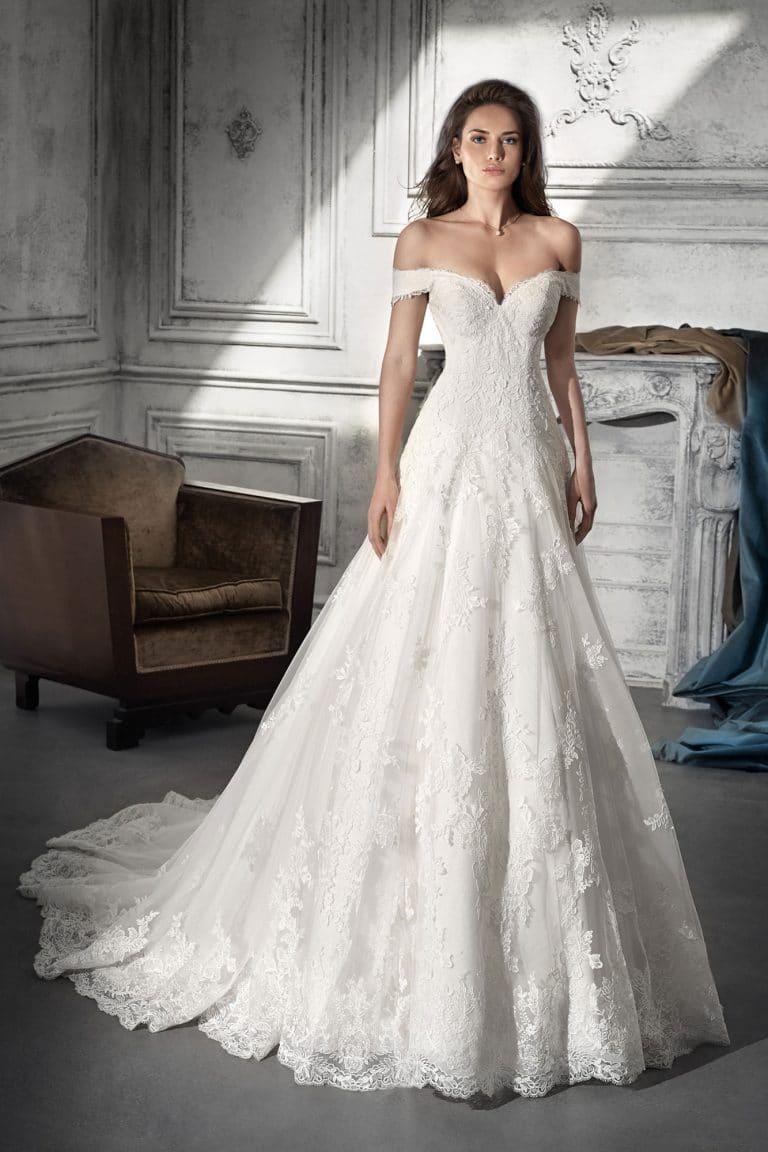 Barna hajú modell pózol egy bérelhető A-vonalú, ejtett vállú Demetrios menyasszonyi ruhában.
