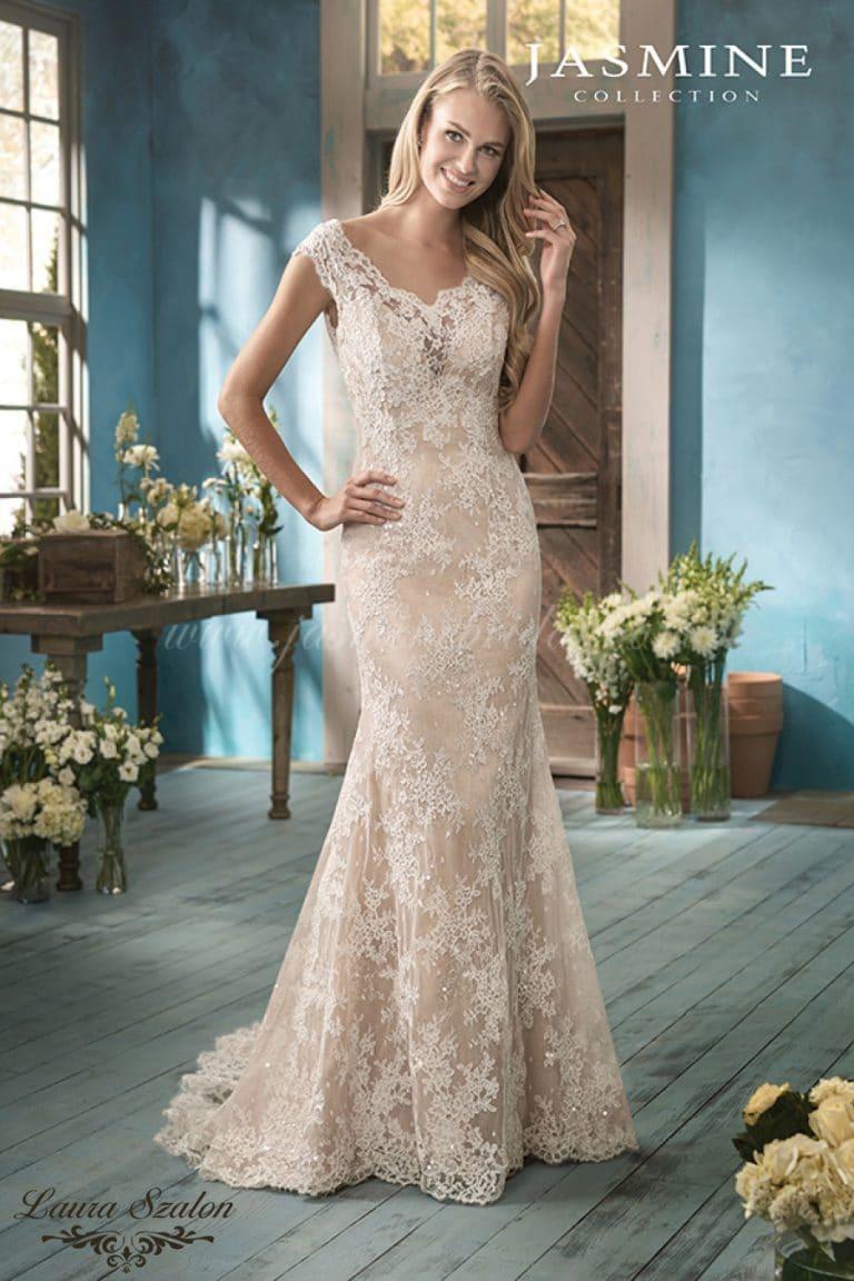 Szőke hajú modell, virágos környezetben egy Jasmine Collection kölcsönözhető menyasszonyi ruhában áll.