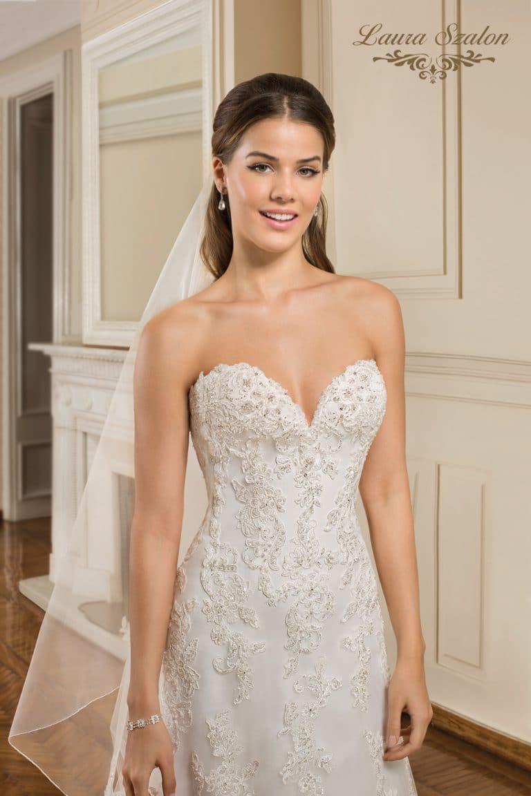 Pánt nélküli, csipkével díszített A-vonalú menyasszonyi ruha.