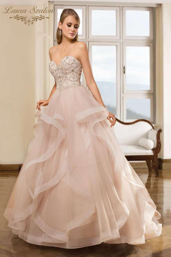 Bérelhető vízhullámos, púder színű Demetrios által tervezett Cosmobella menyasszonyi ruhában áll modellt egy lány.